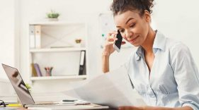 Woman talking on the phone and reviewing paperwork