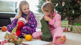 Two girls in pajamas opening their stockings