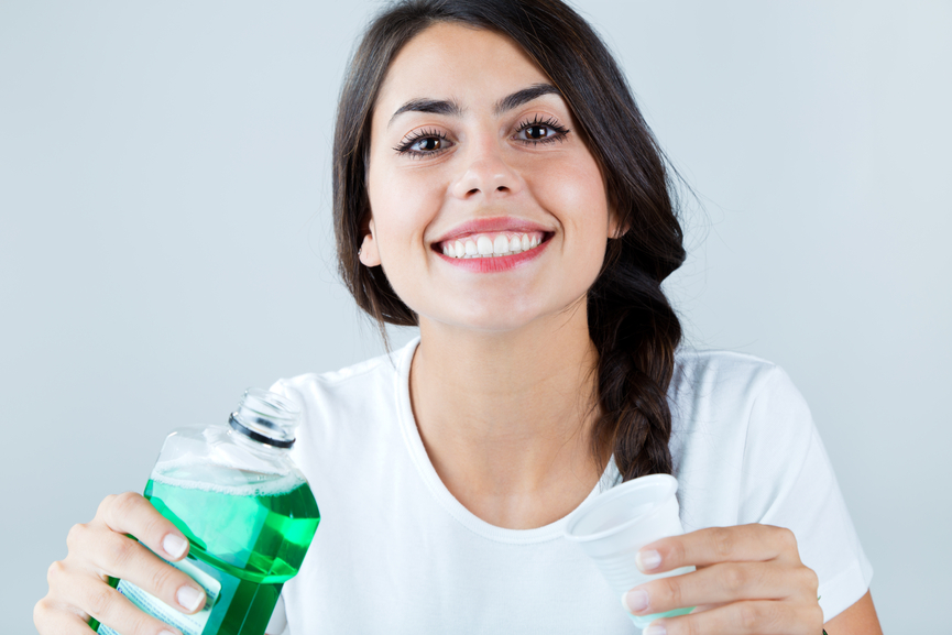 Portrait of girl using mouthwash