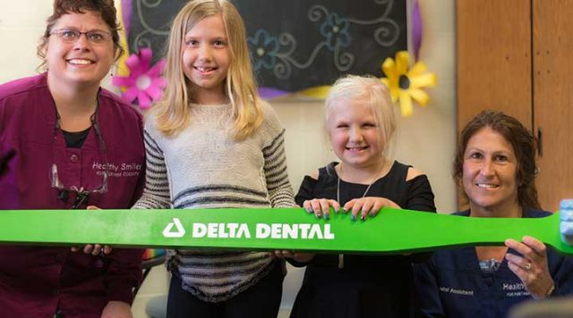 Two hygienists hold a large, green Delta Dental toothbrush with two school-aged girls