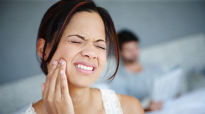 Woman winces from tooth pain