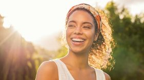 Smiling woman standing outside with the sun behind her