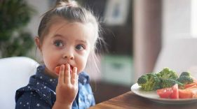 Young girl eating a tomato from a plate of vegetables