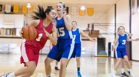 Girl playing basketball dribbles past her opponent