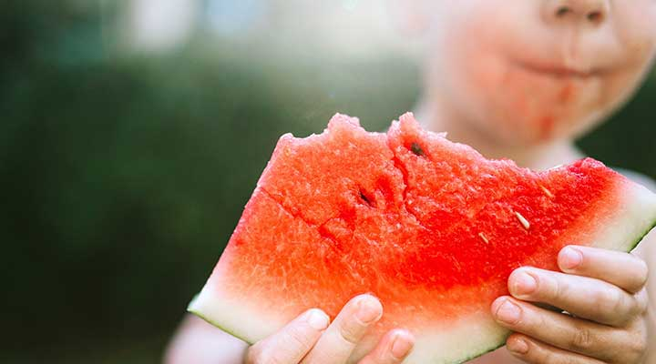 Kid holding out a large piece of watermelon that he is eating