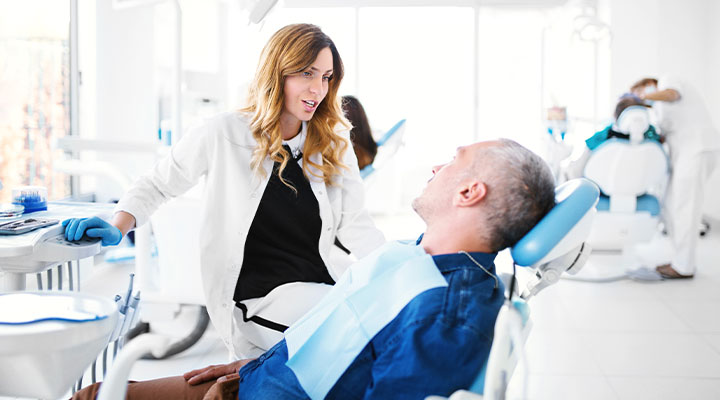 Hygienist talking with a dental patient