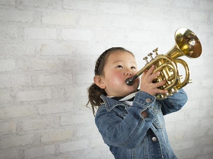 A young girl plays a horn instrument.]